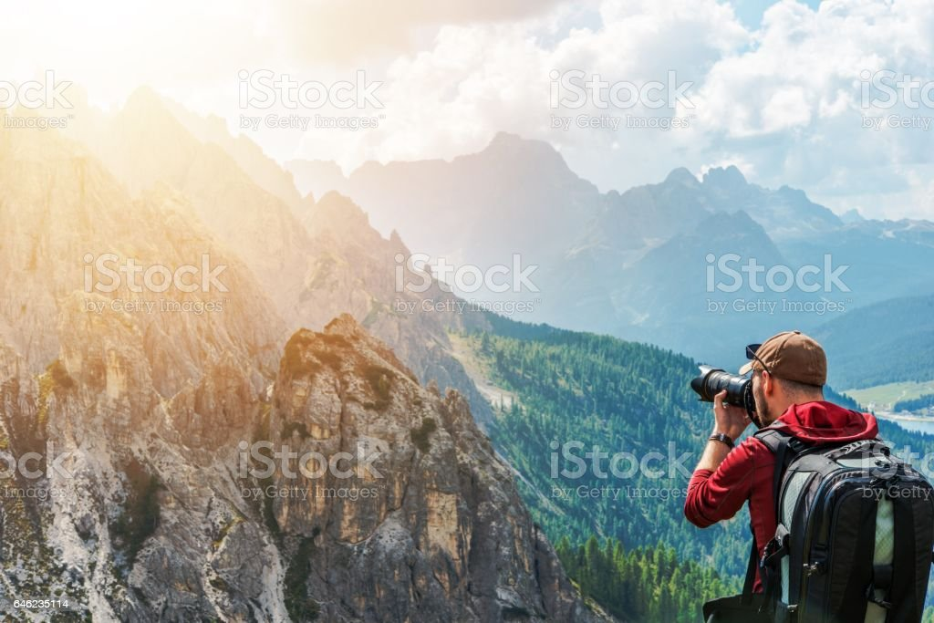 Caucasian Photographer in His 30s and the Wilderness. Photo Session in the Italian Alps. Taking Scenic Pictures. stock photo