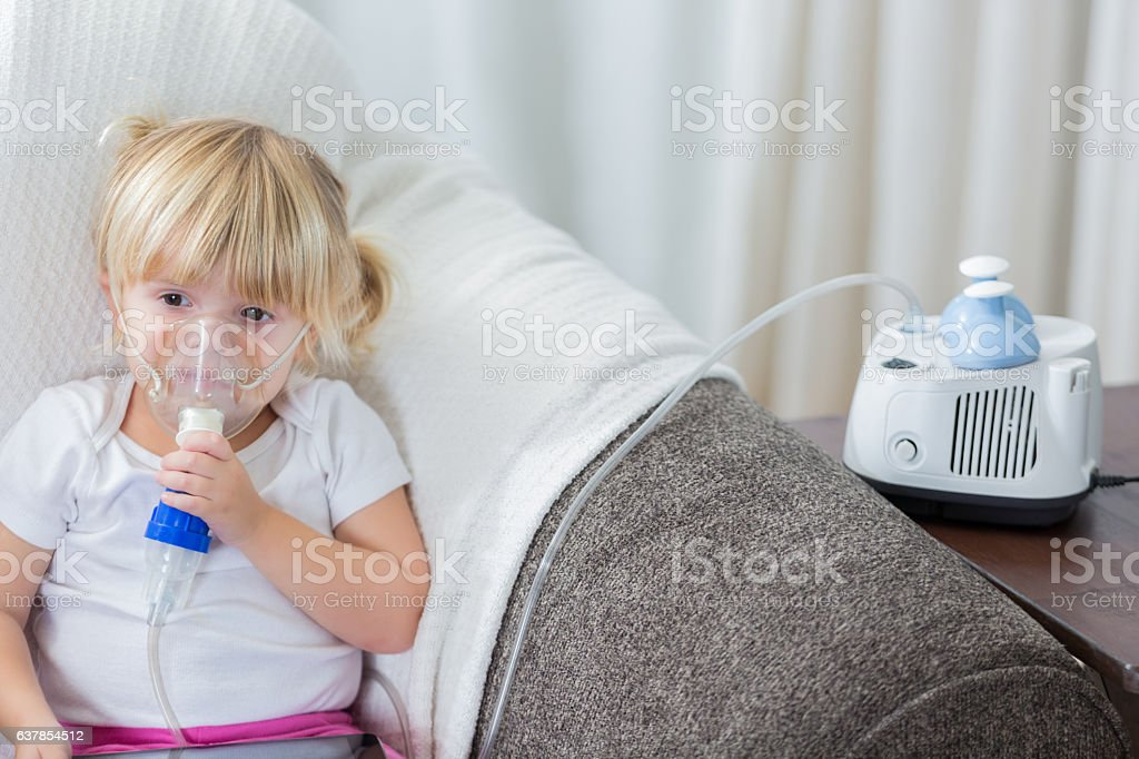 Caucasian preschool age girl with cystic fibrosis receives breathing treatment stock photo