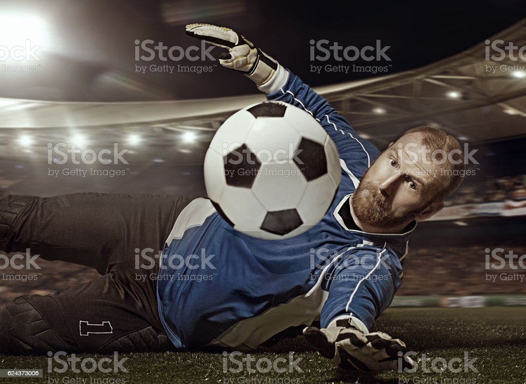 Caucasian redhead adult male soccer player goalkeeper saving football stock photo