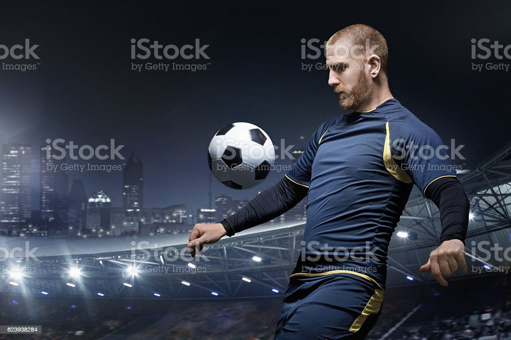 Caucasian redhead adult male soccer player kicking football in stadium stock photo