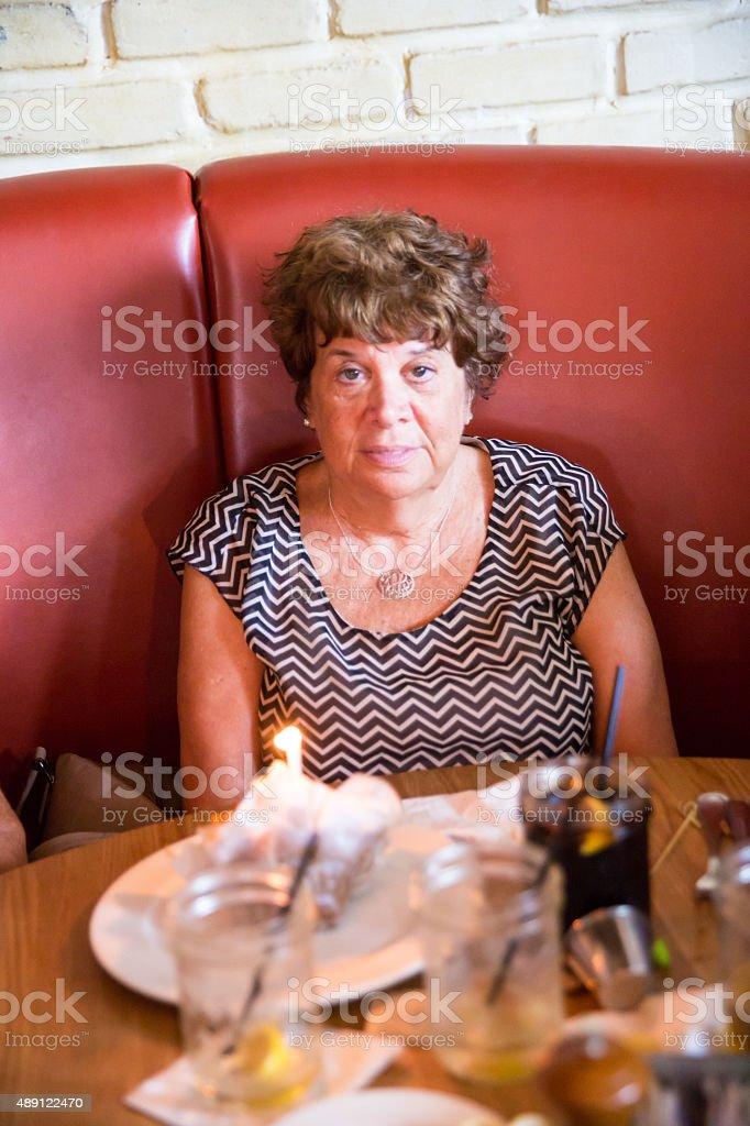 Caucasian senior woman celebrating her birthday in a restaurant stock photo