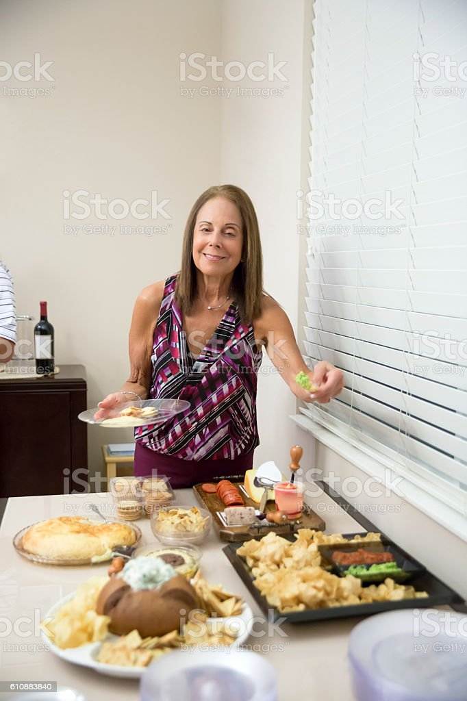 Caucasian senior woman eating at party buffet table stock photo
