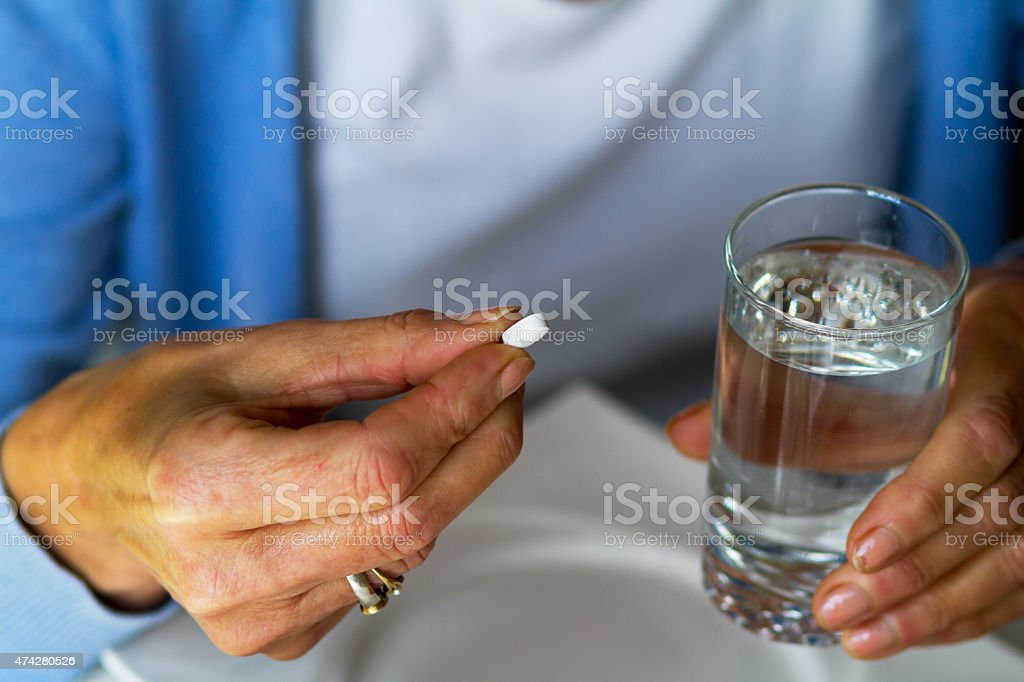 Caucasian senior woman taking cardiac pill stock photo