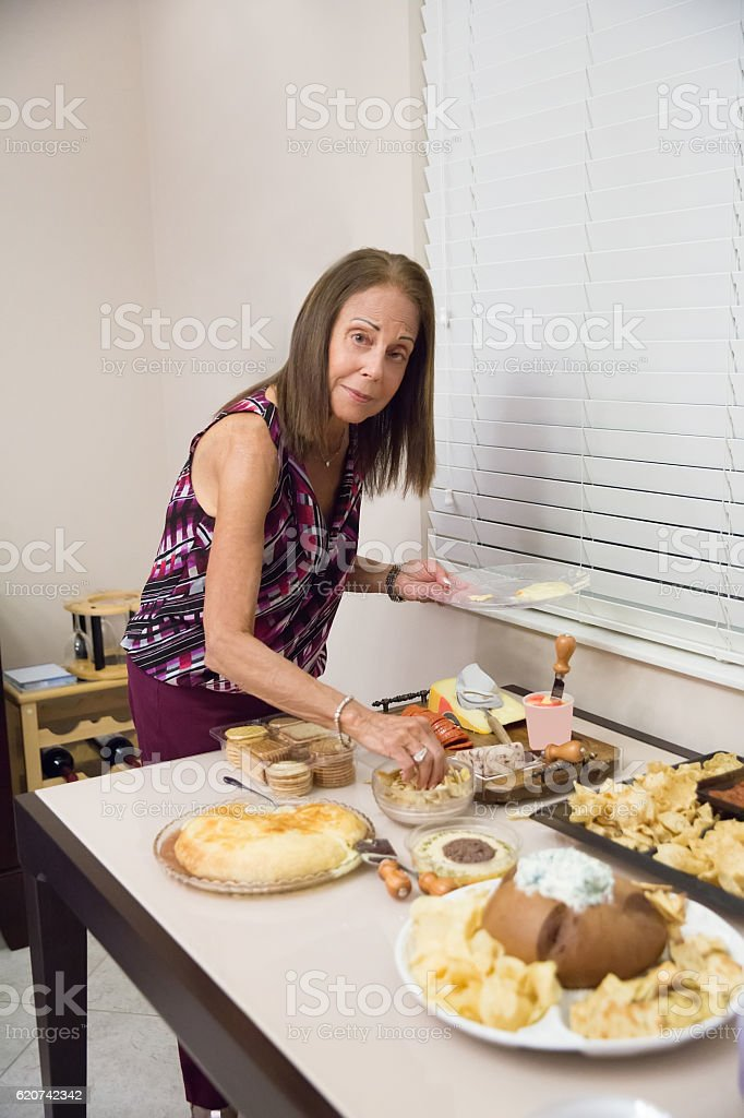 Caucasian senior woman taking food from buffet table at party stock photo