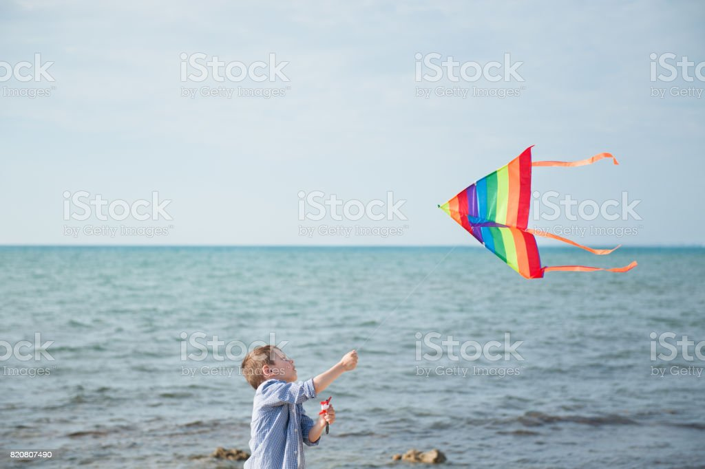 caucasian small boy holding a kite flying in the sky on the background of sea stock photo
