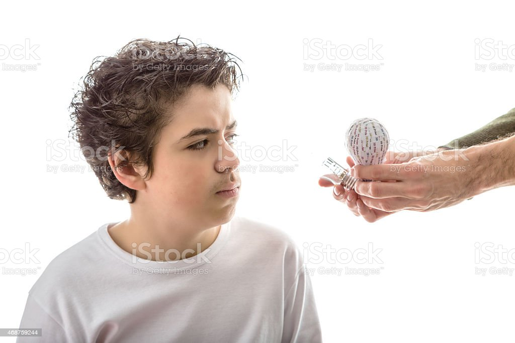 Caucasian smooth-skinned boy puzzled by 3d and real lightbulbs stock photo