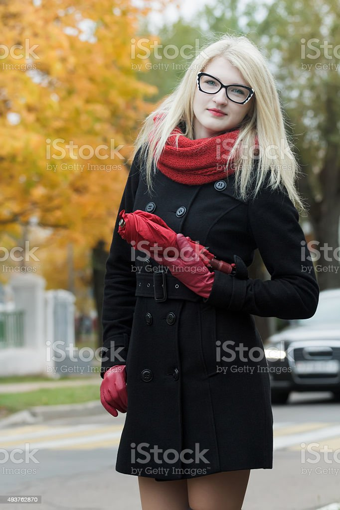 Caucasian student girl with red fully collapsible umbrella in hands stock photo