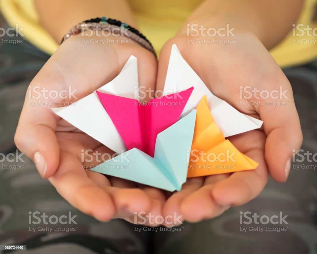 Caucasian teenage girl holding paper airplanes. stock photo