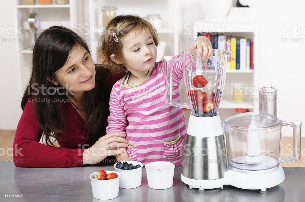 Caucasian Toddler Helping Her Mother Preparing A Smoothie royalty-free stock photo