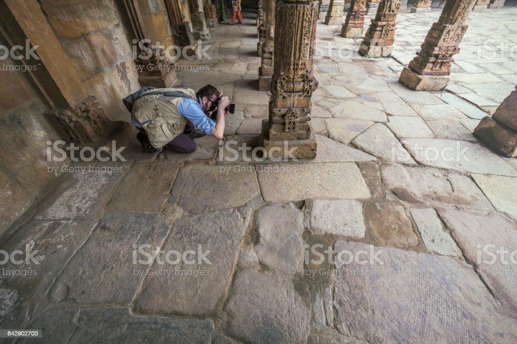 Caucasian tourist photographing Qtub Minar's architecture stock photo