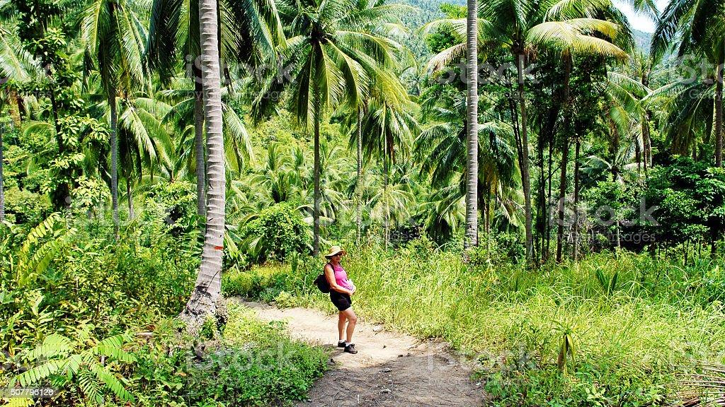 Caucasian tourist walking on jungle path in Koh Samui,Thailand stock photo