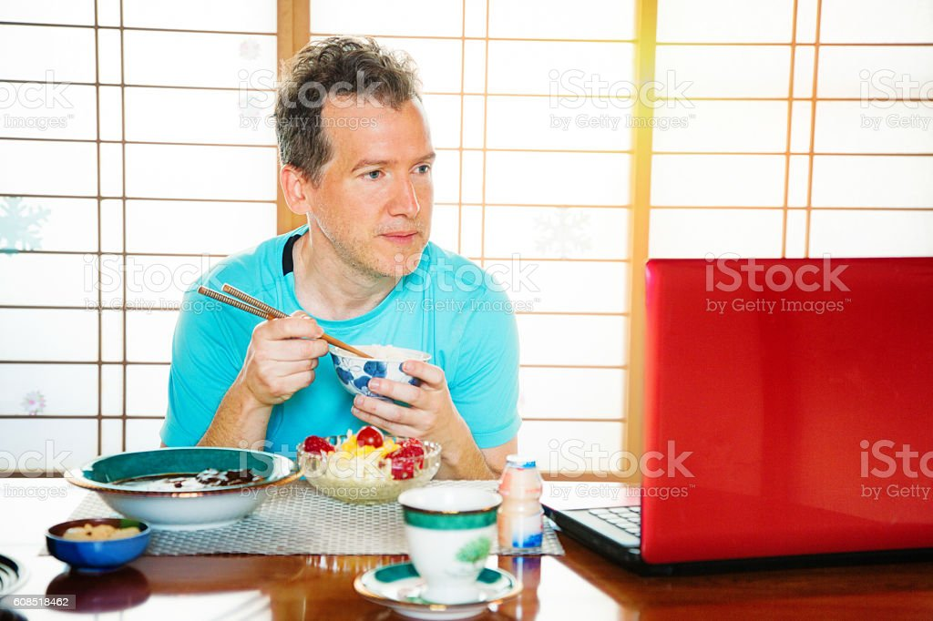 Caucasian tourist watching media on laptop while eating Japanese food stock photo