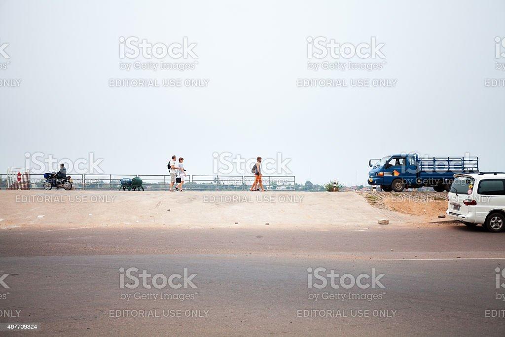 Caucasian tourists walking along promenade at Mekong in Vientiane stock photo