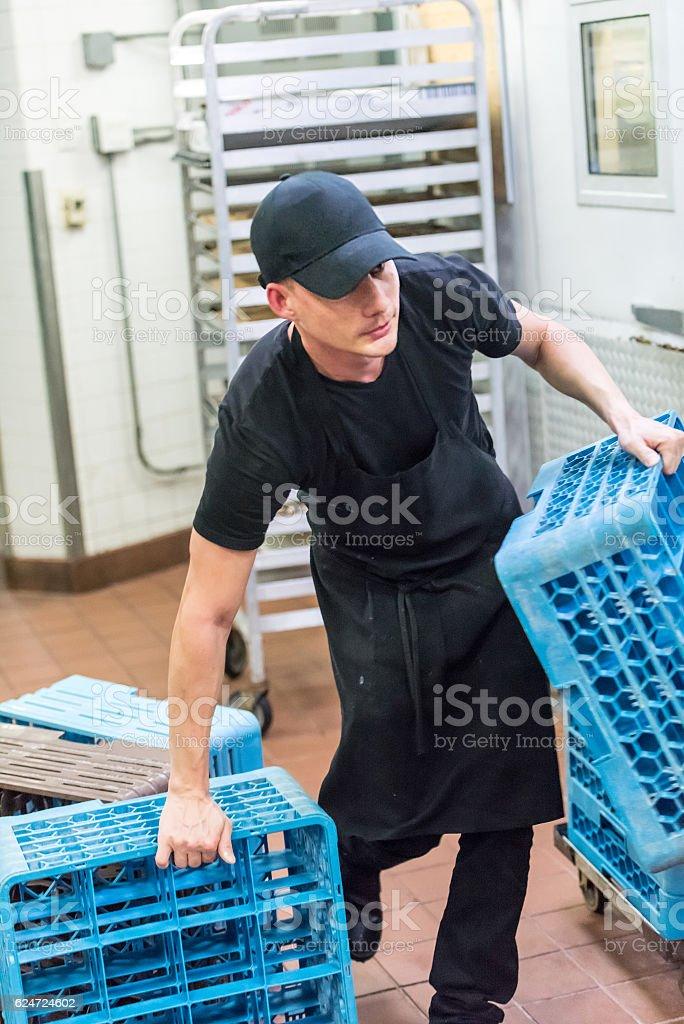 Caucasian waiter busboy working at the kitchen stock photo