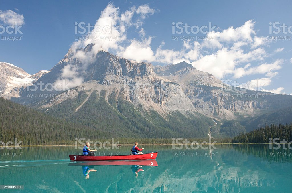 Caucasian Woman and Boy Canoeing on Emerald Lake stock photo