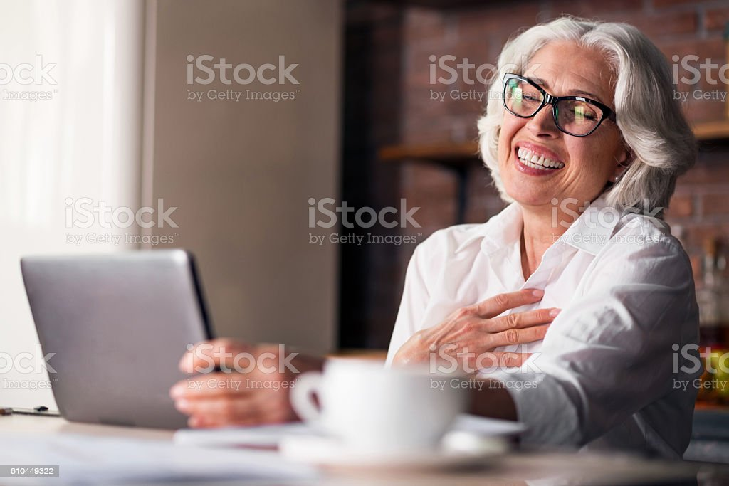 Caucasian woman being happy using computer for family communication stock photo