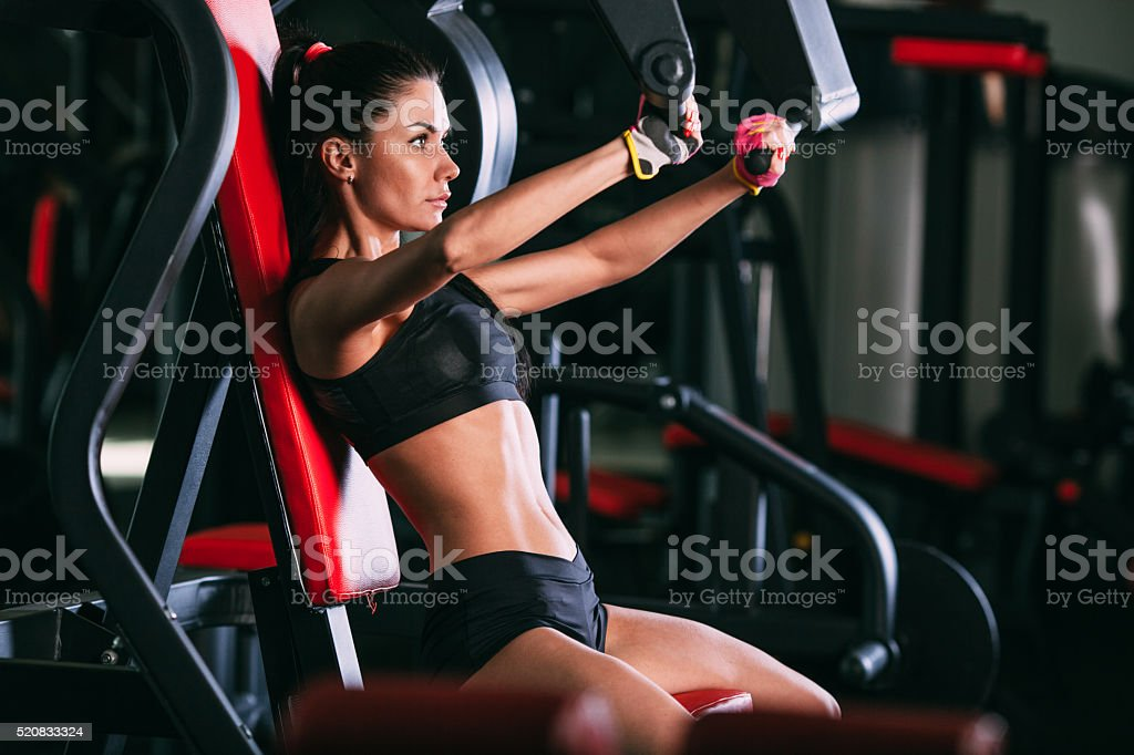 caucasian woman exercising on shoulder press machine stock photo