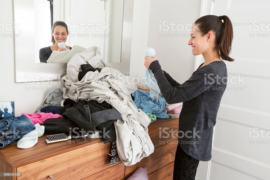 Caucasian woman folding a pile of clean laundry stock photo