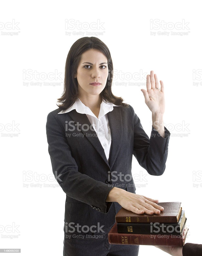Caucasian Woman Hand Raised Swearing on a Stack of Bibles royalty-free stock photo