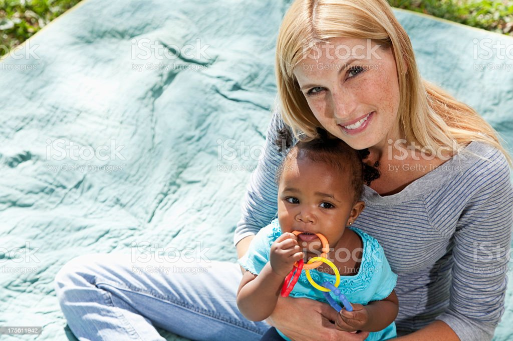 Caucasian woman holding African American baby stock photo