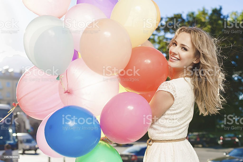 Caucasian woman holding colorful balloons in the sunshine royalty-free stock photo