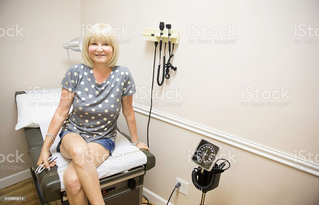 Caucasian woman in Doctor's exam rooom for yearly physical stock photo