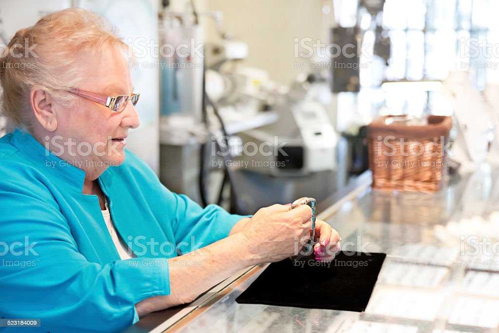 Caucasian woman jewelry store owner holding a watch stock photo
