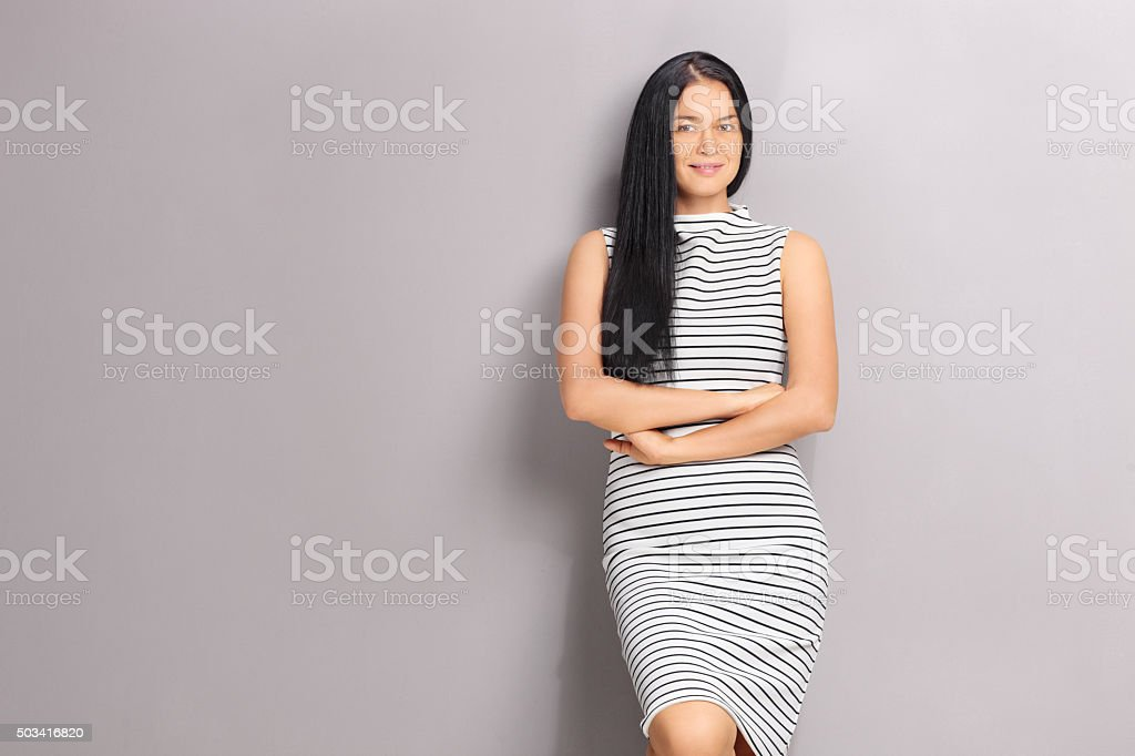 Caucasian woman leaning against a gray wall stock photo