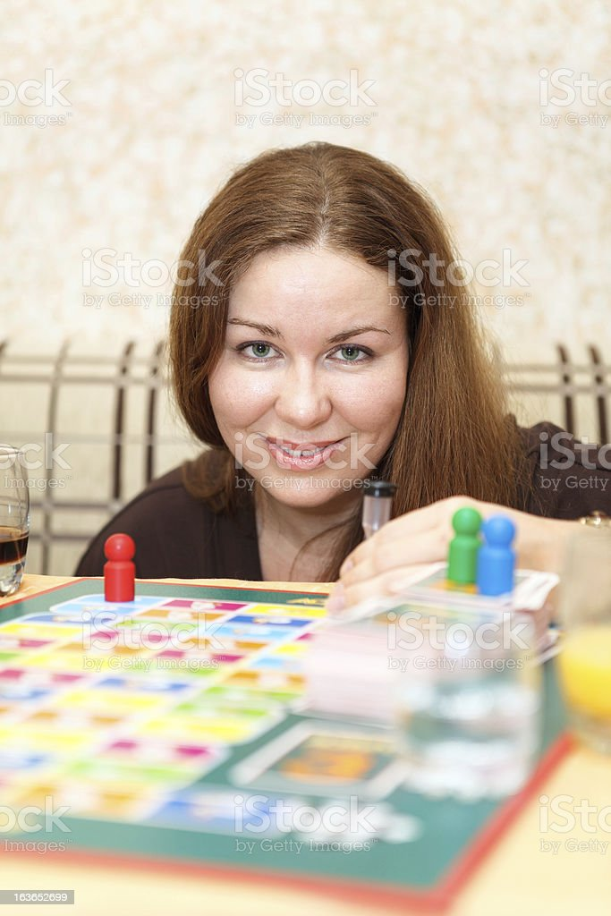 Caucasian woman playing board games in domestic room royalty-free stock photo