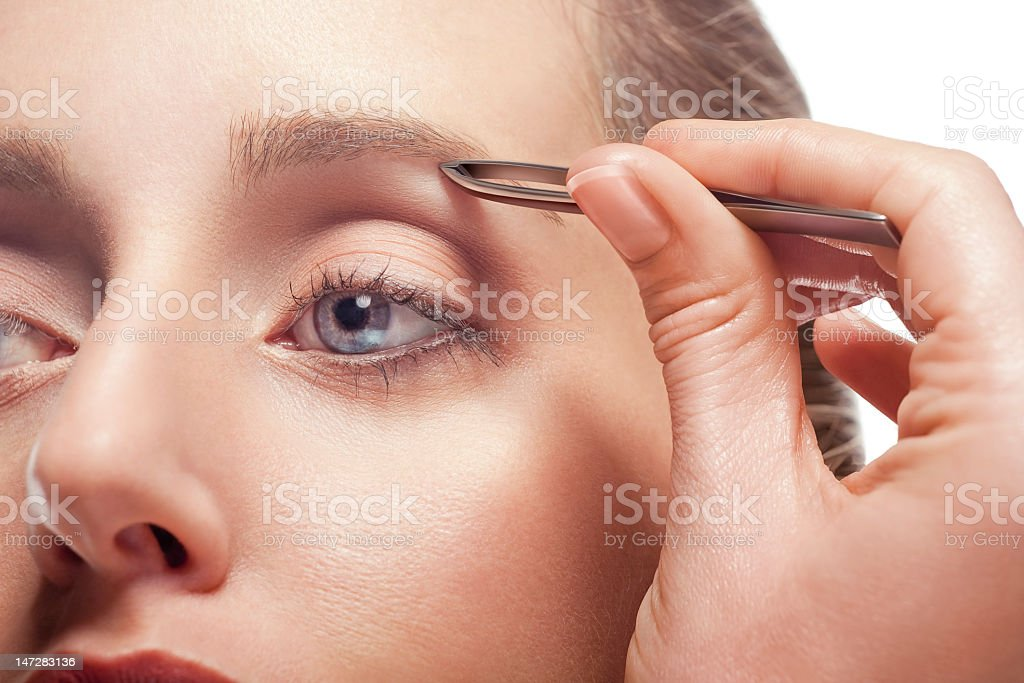 Caucasian woman plucking eyebrow with tweezers stock photo