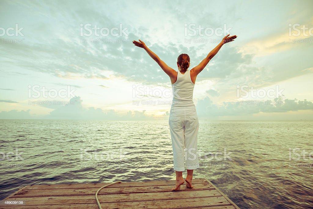 Caucasian woman practicing yoga at seashore stock photo