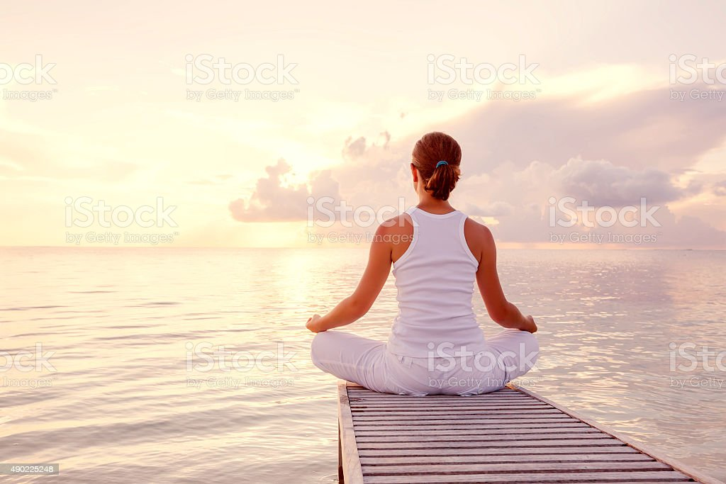 Caucasian woman practicing yoga at seashore stock photo