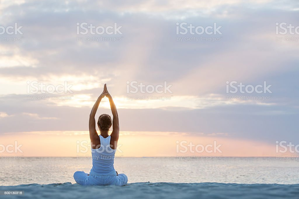 Caucasian woman practicing yoga at seashore royalty-free stock photo