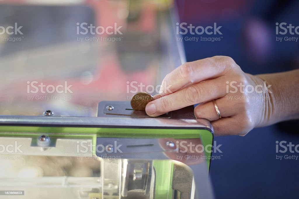 Caucasian woman putting coin in slot machine royalty-free stock photo