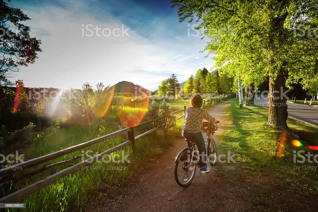 Caucasian Woman Riding Bike at Sunset in Countryside stock photo