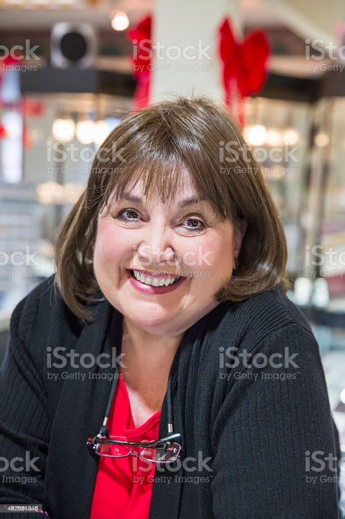 Caucasian woman salesperson smiling in jewelry store stock photo