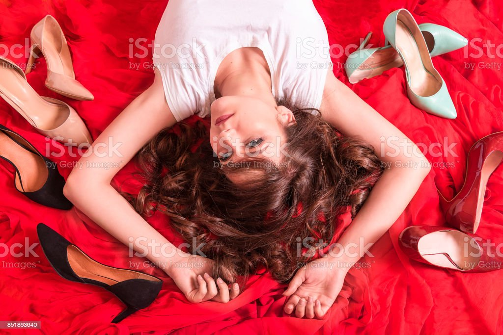 Upside down view of a young, beautiful woman with blue eyes and red...