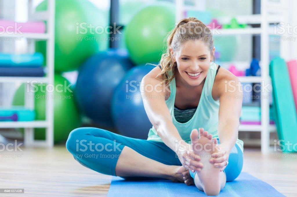 Attractive mid adult woman smiles as she touches her toes on the...