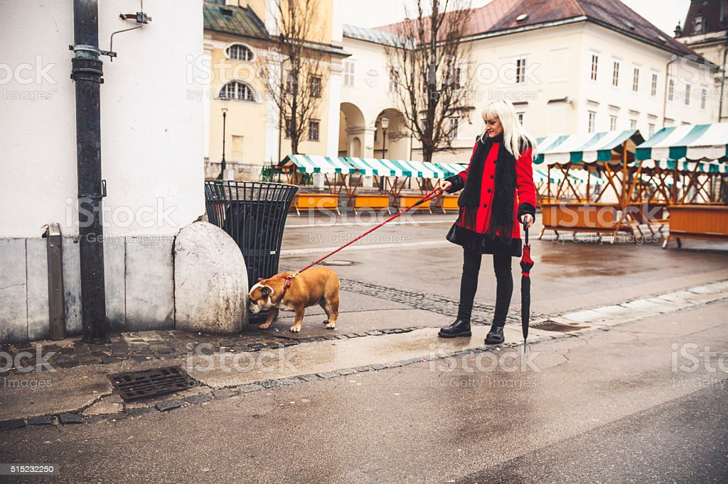 Mid adult Caucasian woman walking the dog in the city, Europe, warm...