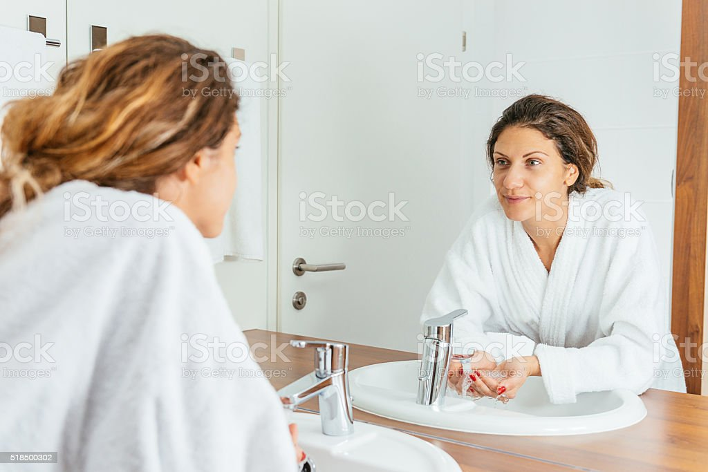 Caucasian woman washing hands and applying skin care soap stock photo
