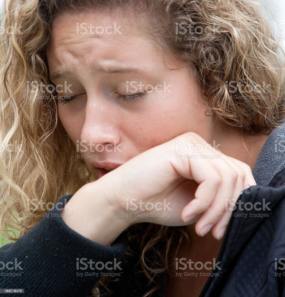 Caucasian woman with blond hair coughs or sneezes stock photo