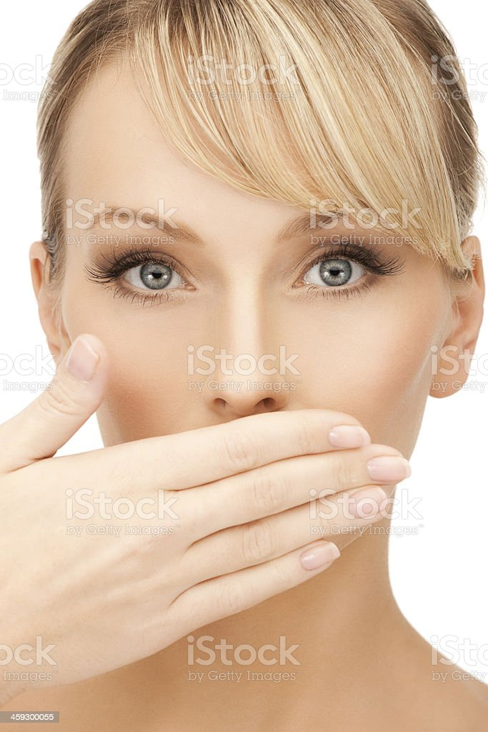 Caucasian woman with blue eyes and hand covering mouth stock photo