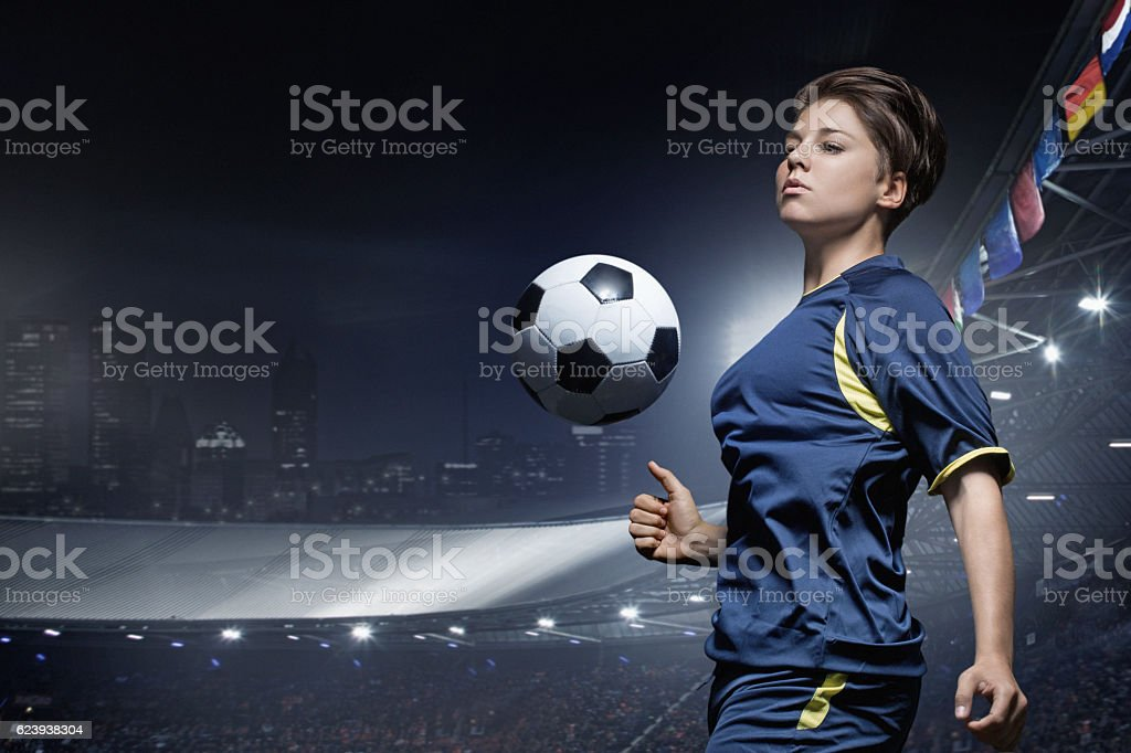 Caucasian young adult female soccer player playing football in stadium stock photo