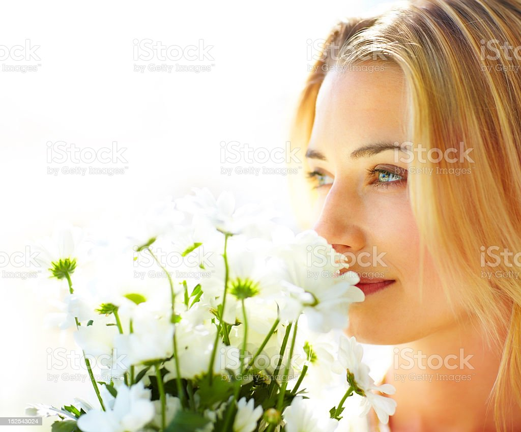 Caucasian young lady enjoying fragrance of flowers royalty-free stock photo
