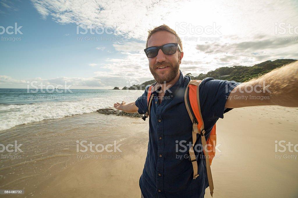 Caucasian young man on beach takes selfie portrait stock photo