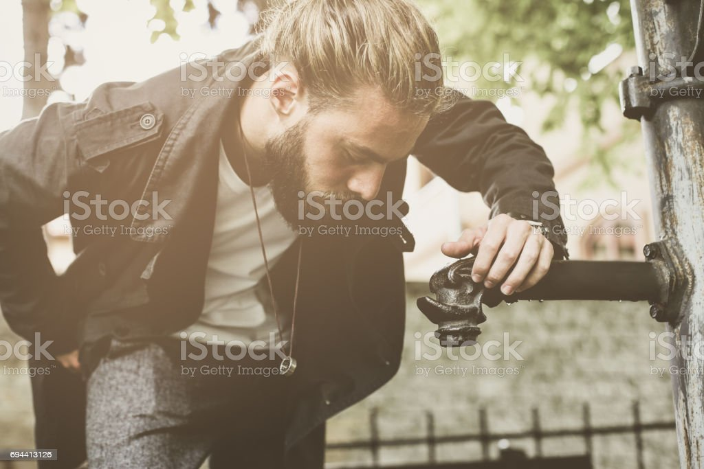Caucasian young man preparing to drinking water from the fountain.