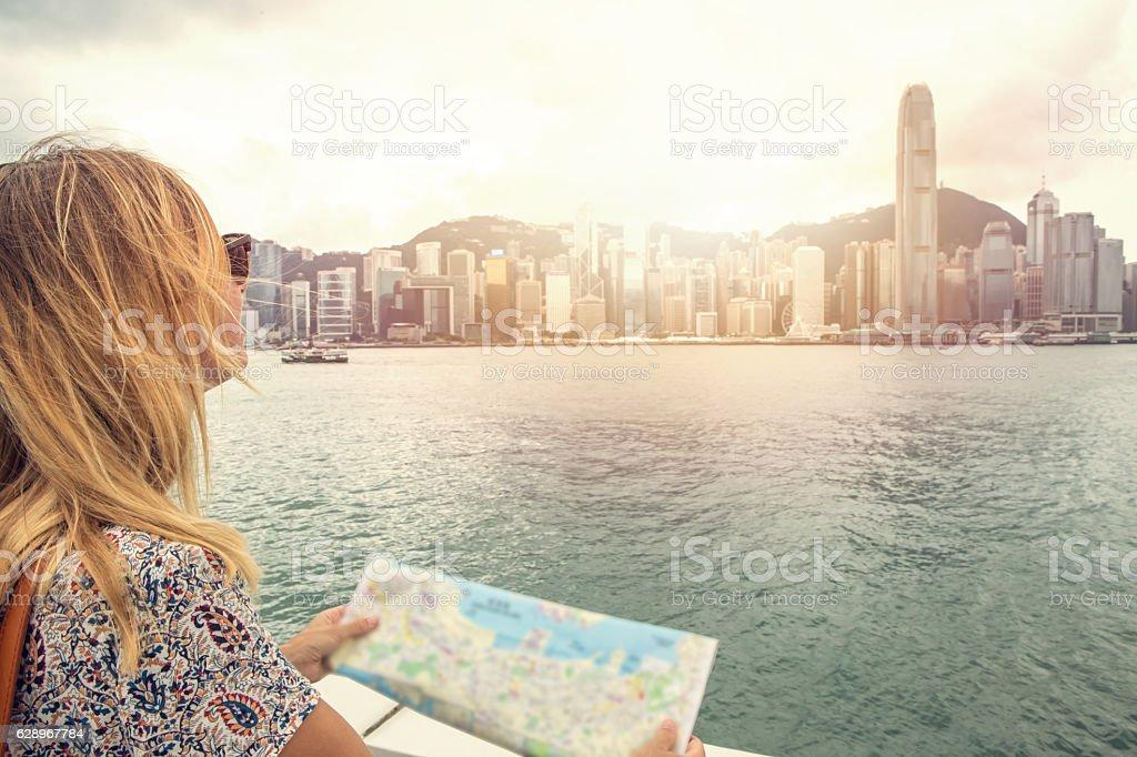 Caucasian young woman looks at Hong Kong city map stock photo