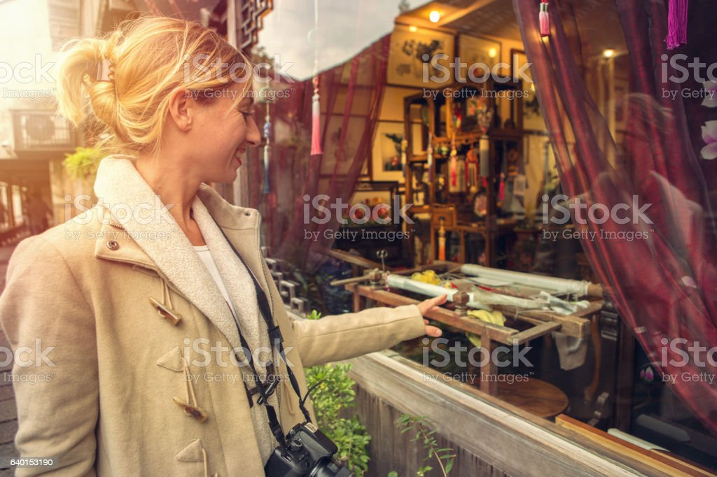 Caucasian young woman window-shopping in China stock photo