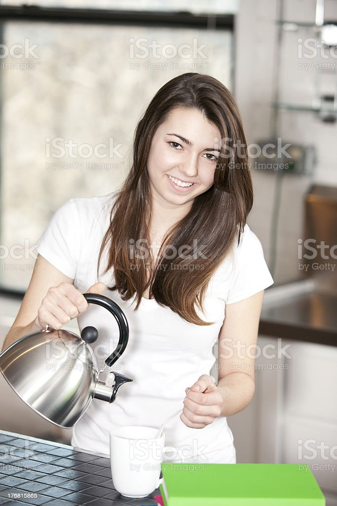 Caucasion Teenage Girl Pouring Cup of Tea in Kitchen royalty-free stock photo