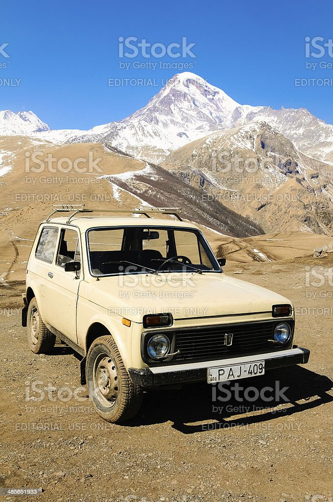 Caucasus mountains in spring with snow and Lada Niva jeep stock photo